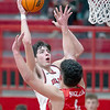 VON CASTOR/Special to the Phoenix<br /> Hilldale's Ty O'Neal shoots over Stigler's Luke Adcock Friday night in the Class 4A Area IV District 7 boys championship game at Hilldale.