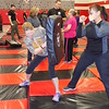 Staff photo by Mike Elswick<br /> Laura Holt, left, braces for a hit from a strike pad from Breanna Faerro during a self-defense training session held for women by the Muskogee Police Department. MPD officers provided women tips on how to to defend themselves if attacked.
