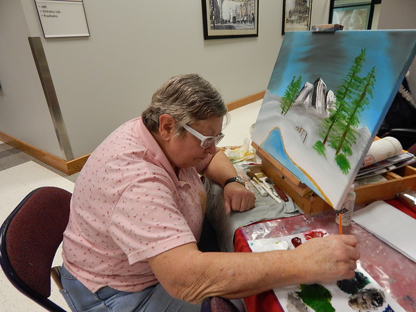 """KENTON BROOKS/Muskogee Phoenix<br /> Lucille Brisson-Dickson of Wagoner works on her oil painting in the Bob Ross Method of using brushes and techniques at the Jack C. Montgomery VA Medical Center on Monday. Brisson-Dickinson, a retired U.S. Army Nursing Corps officer, said she's """"more relaxed"""" when she's painting. She entered the center's art competition."""