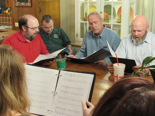 CATHY SPAULDING/Muskogee Phoenix<br /> Okiepella singers, from left, Jeremy Jones, Eddie Yadon, Ken Herringshaw and Tim Matthews practice around the table. The a cappella singing group will perform two concerts Saturday and Sunday at Muskogee Church of Christ.