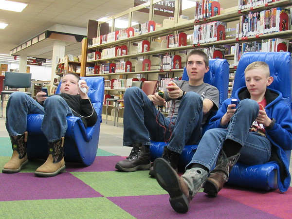CATHY SPAULDING/Muskogee Phoenix<br /> Three brothers, from left, Mason Harris, Dylan Harris and Blake Harris, battle it out on a TV video game Wednesday at the Muskogee Public Library. Freezing temperatures sent people seeking warmth in the library.