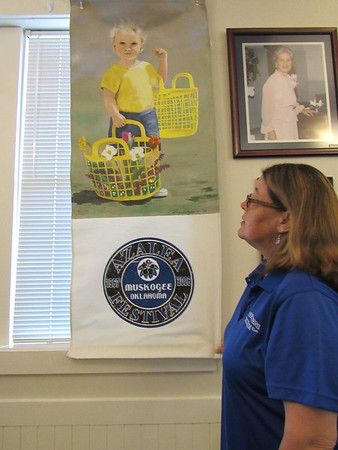 CATHY SPAULDING/Muskogee Phoenix<br /> Three Rivers Museum Director Angie Rush adjusts a daffodil-themed banner, which is among several to be shown during the Daffodil Day arts and crafts show on Saturday.