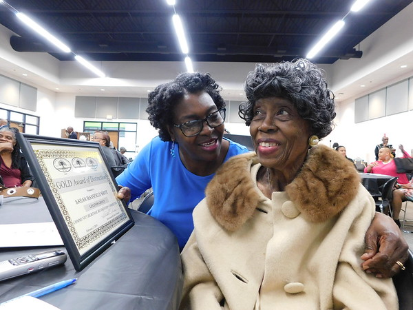 CATHY SPAULDING/Muskogee Phoenix<br /> Caretaker Wanda Ross, left, shows retired Indian Capital Technology Center business teacher Sarah Mansfield White the Legend plaque White received at the Legacy Keepers R Us Honors Bruncheon, held Saturday.