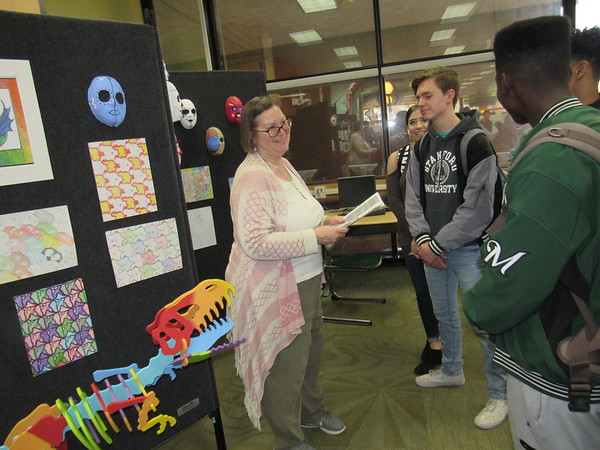 Muskogee High School teachers hosted a Fine Arts and Humanities Fair on Thursday to encourage MHS freshmen to consider classes such as choir, drama, German, Spanish and fine arts when they enroll for the 2019 school year. Muskogee High School arts and crafts<br /> teacher Sonjya Kadlec, left, tells MHS students about what her class offers them.