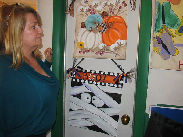 CATHY SPAULDING/Muskogee Phoenix<br /> Lori Martin finds a relaxing and creative outlet painting banners, including a couple of seasonal ones hanging in her garage.