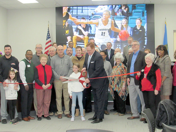 CATHY SPAULDING/Muskogee Phoenix<br /> Muskogee city and school officials, plus business leaders and children surround Muskogee School Superintendent Jarod Mendenhall as he holds the scissors for the recent Muskogee Public Schools Education Service Center ribbon cutting and open house.
