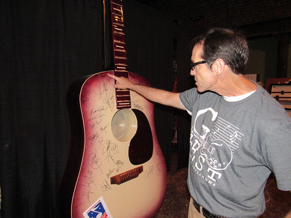 Staff photo by Cathy Spaulding<br /> Ron Boren of the Oklahoma Music Hall of Fame points out some of the autographs on an acoustic guitar statue on display at OMHOF. Performers at G Fest's main stage signed the guitar.