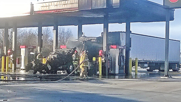 """Staff photo by Ronn Rowland<br /> A tractor-trailer rig caught fire in a diesel fueling bay at QuikTrip on Tuesday afternoon, said Assistant Fire Chief Gordon Lee. The truck, which was hauling a refrigeration unit, pulled underneath a west diesel bay with an awning. """"We're not sure what caused the cab to catch fire but it was completely engulfed in flames and completely burned up,"""" Lee said. The metal awning above it was scorched.Initially a pumper truck was dispatched to the scene but another one was soon requested from another station, Lee said. Firefightersused foam to extinguish the fire because foam is a wetter substance and suffocates the fire. The store's manager turned off that row of pumps from inside the convenience store. The driver received a small burn on his arm but didn't request medical attention."""