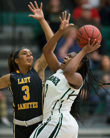 Phoenix special photo by Von Castor<br /> Muskogee's Chris'alee Patterson, right, puts up a shoot in the lane as Sand Springs' Kierra Mcgee defends Tuesday at Ron Milam Gymnasium.