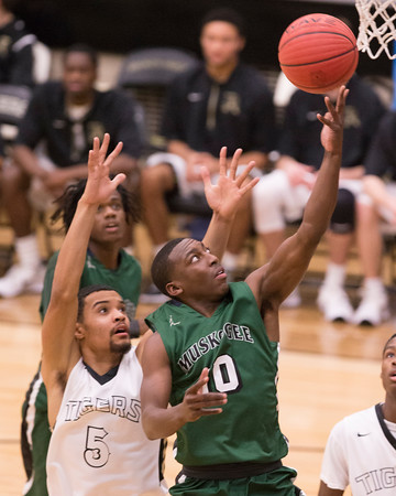 Special photo by Von Castor<br /> Muskogee's Chris Mims scores in the lane in front of Broken Arrow's Tony Hall Tuesday night at Tiger FieldHouse in Broken Arrow.
