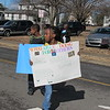 Staff photo by Cathy Spaulding<br /> Serenity Burkhalter carries a handmade poster reflecting the theme of Monday's Martin Luther King Day Parade while marching past youth from St. Mark Baptist Church.