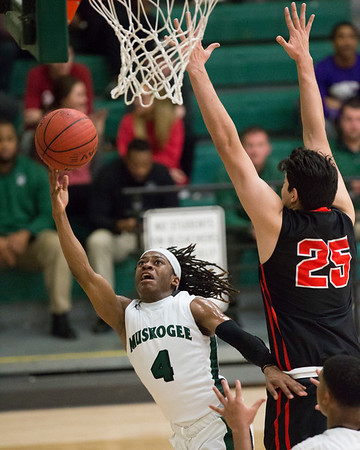 Phoenix special photo by Von Castor<br /> Muskogee's Tyreece Berry, left, tries to get a shot off in the lane around Tulsa Union's Adrian Rodriguez Tuesday at Ron Milam Gymnasium.