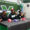Staff photo by Mike Kays<br /> Muskogee's Kamren Curl, center, sits with his family after verbally committing on Thursday to the University of Arkansas.