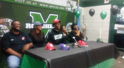 Staff photo by Mike Kays Muskogee's Kamren Curl, center, sits with his family after verbally committing on Thursday to the University of Arkansas.