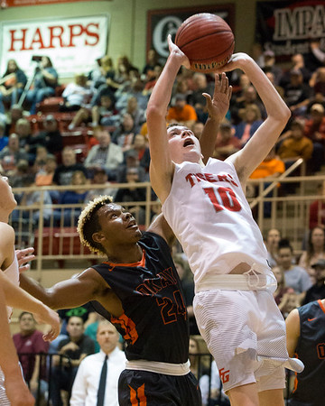 Phoenix special photo by Von Castor Fort Gibson's Jace Shepherd, right, puts up a shot in front of Okay's Darius Riggs during Saturday's boys championship game of the Old Fort Classic at Harrison Field House. The Tigers won 69-52.