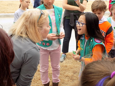 Special photo by Mike Elswick Chief Executive Officer of the Girl Scouts of Eastern Oklahoma Roberta Preston gets a surprised look from Sophie Vaughn with Troop 2173 from Tulsa during Saturday's event in the Muskogee Arts District commemorating the centennial of Girl Scout Cookie sales.