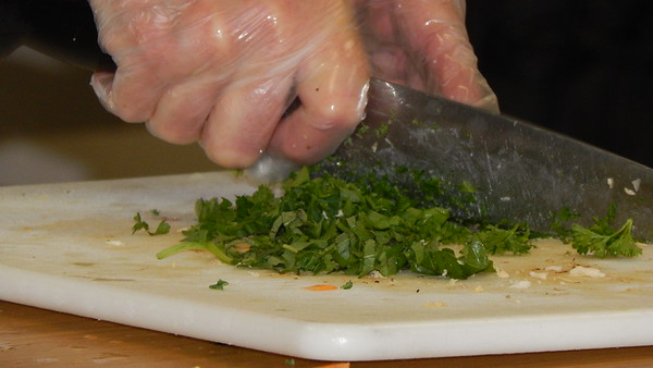 Staff photo by Cathy Spaulding<br /> Muskogee Public Schools Chef Neda Hilliard keeps fingers out of the way while chopping parsley. She says fragile parsley should be added toward the end of cooking.