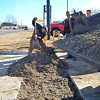 Staff photo by Mark Hughes<br /> Eric Woods, water operator, prepares to break apart the dirt just dumped after the crew repaired a 6-inch cast iron pipe last week that was around 50 years old. Todd Garner, in-town maintenance supervisor, said that it took four hours just to get through the concrete, so they're putting down asphalt.