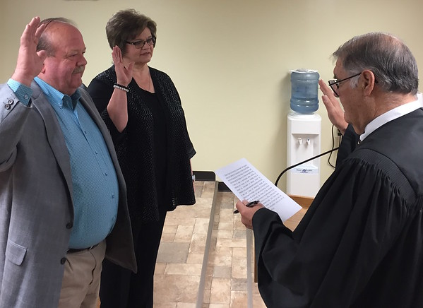 Staff photo by D.E. Smoot<br /> Muskogee County District Judge Mike Norman, right, administers the oath of office on Tuesday to District 2 Commissioner Stephen Wright, left, and County Clerk Dianna Cope. Court Clerk Paula Sexton and incoming Sheriff Rob Frazier were sworn into office during a separate ceremony later in the day.