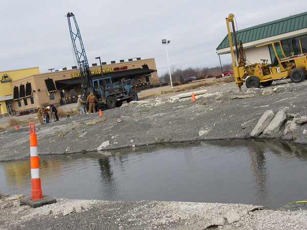 Staff photo by Cathy Spaulding<br /> A space for gas station tanks is filled with water as workers with Rossco Construction prepare the ground for a new Panda Express Chinese Kitchen on the site of an old convenience store at the corner of 11th Street and Shawnee Bypass.