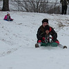 Staff photo by Cathy Spaulding<br /> Gabby Plunkett, 8, lifts her feet as she sleds down Civitan Park's hill with her cousin Tristan Jacobson, 17, Friday. Morning snow and sub-freezing temperatures brought danger and delight to the Muskogee area. District 1 Muskogee County Commissioner Ken Doke said crews were out early Friday morning clearing and sanding roads. Steep roads, including Country Club Road between Gibson and North Streets, were closed Friday morning.