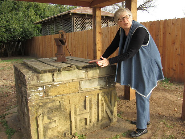 Staff photo by Cathy Spaulding<br /> Retired Fort Gibson teacher Thrissa Johnson shows stonework around the Roselawn water pump. She said it came from a store run by Roselawn builder Florian Nash.