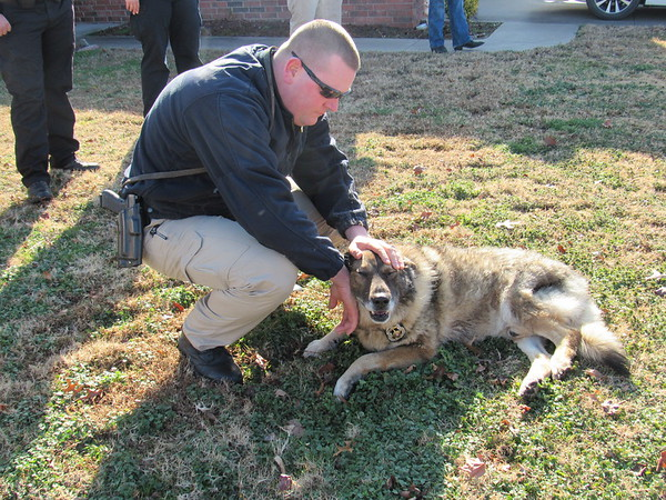 CATHY SPAULDING/Muskogee Phoenix Fort Gibson Police officer Brent Maddocks comforts retired police dog, Boss, before the dog was euthanized on Friday. Boss received a police escort.