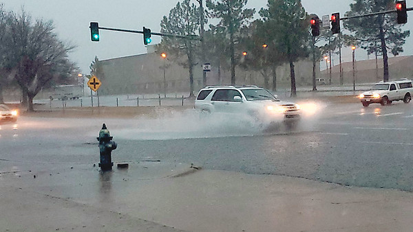 CHESLEY OXENDINE/Muskogee Phoenix<br /> Standing water curtains up around a car traveling through the intersection of Seventh Street and Okmulgee Avenue Friday afternoon.