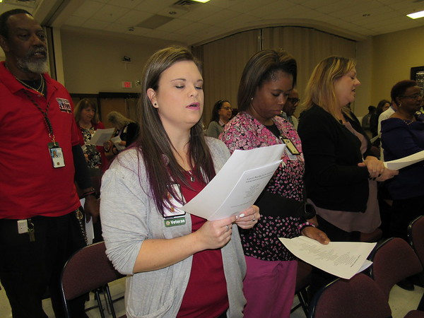 """Staff photo by Cathy Spaulding<br /> Jack C. Montgomery VA Medical Center employees, from second left, Cindy Kroll, Lanise Jamerson and Stacie Williams sing """"Lift Every Voice and Sing"""" at the opening of the medical center's Dr. Martin Luther King Jr. program Friday."""