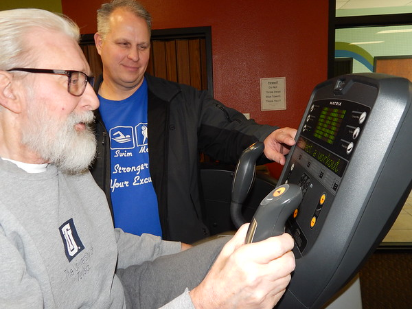 Staff photo by Cathy Spaulding<br /> Kent Kamp shows Walter Mazil of Wagoner how to adjust his stationary bicycle workout monitor. Kamp has been with Muskogee Swim and Fitness since it opened 10 years ago.