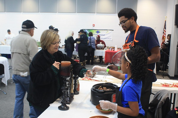 Special photo by Chesley Oxendine<br /> Carolyn Mayes, left, samples some brisket from Sydney Nelson and his younger sister Taylor Nelson.