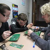 CATHY SPAULDING/Muskogee Phoenix<br /> Fort Gibson Middle School students, from left, Lauren Compton and Jonathan Gifford, watch STEM teacher Chris Staton demonstrate soldering on an electronic board, part of a kit Staton bought with a Fort Gibson Education Foundation grant.
