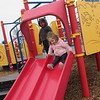 CATHY SPAULDING/Muskogee Phoenix<br /> Ozzy Sam, left, watches playmate Kenny Parks go down the slide at Civitan Park's playground on Tuesday. Both are about 1 and a half years old. Mild weather drew people to the park. The playground had been fenced in until recently as crews work on a new splash pad, restroom facilities and covered picnic area at the park.
