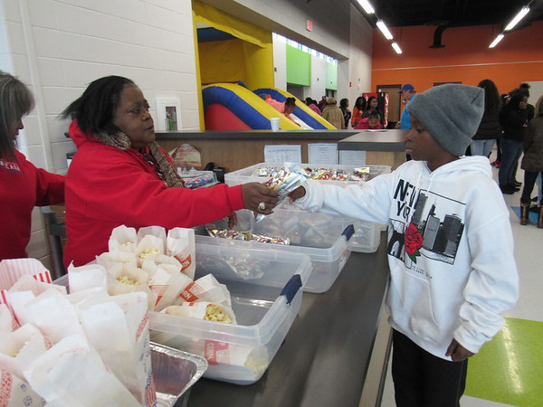 Staff photo by Cathy Spaulding<br /> Brenda Derrick hands a free hot dog to Damarius Williams, 11, at the Dr. Martin Luther King Jr. Community Center on Monday after the Martin Luther King Jr. Day Parade. Hundreds packed the warm center after the parade.