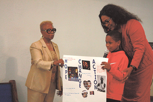 Special photo by Chesley Oxendine<br /> Laura Wade, left, and Brenda Davison, right, present Christopher Pace as the winner of the Fifth annual Youth<br /> Oratorical/Poster Contest's elementary poster category.