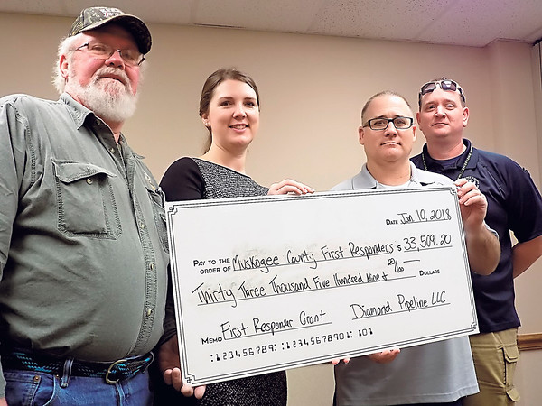 Staff photo by Mike Elswick<br /> From left: Keefeton Assistant Fire Chief Rusty Dornan, Diamond Pipeline representative Karen Rugaard, Muskogee County Sheriff Rob Frazier and Jeff Smith, county emergency management director, pose with a facsimile check representing the $33,500 donation the pipeline firm made to area first responder groups.