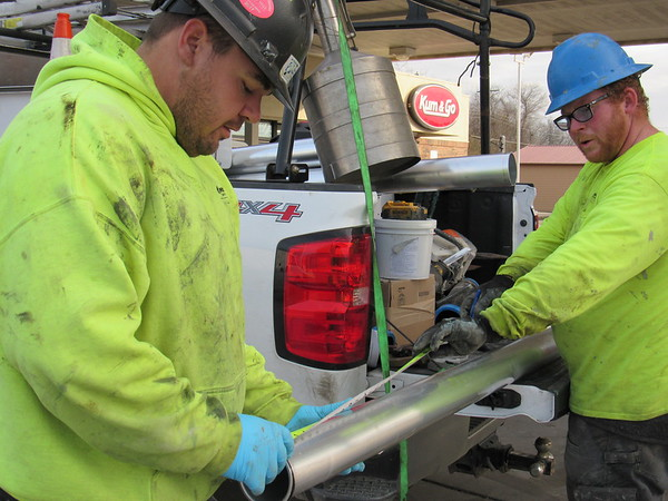 CATHY SPAULDING/Muskogee Phoenix<br /> Andrew Harman, left, and Ty Mills measure a pipe Monday afternoon. Workers with Seneca Co. worked on replacing a spill bucket and other underground equipment outside the Kum & Go convenience store at 32nd and Arline streets.