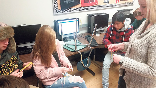 Staff photo by Cathy Spaulding<br /> Hilldale High students, from left, Luke Hansen, Immajen Brown and Nika Alexander follow instructions by their teacher, Tera Shows, right, on how to spin a dream catcher. The craft is part of Shows' Native American history and culture class.