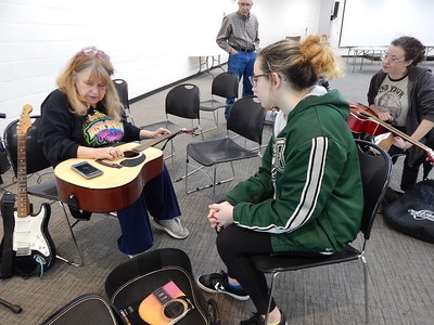 KENTON BROOKS/Muskogee Phoenix Selby Minner, left, tunes Hadleigh Smith's guitar prior to giving her and others lessons at the Dr. Martin Luther King Jr. Community Center. Taylor Blake, right, and A.C. Lorenz listen. Minner has been teaching guitar for 14 years.