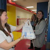 CATHY SPAULDING/Muskogee Phoenix<br /> Hilldale Elementary teacher Melanie Flinn, left hands a bag of dry erase markers to Parent Teacher Organization President Kawana Dick, right, while Principal Patti Bilyard watches.