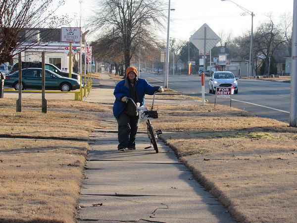 Staff photo by Cathy Spaulding<br /> After a morning low of 2 degrees, temperatures rose to 31 egrees and brought a trickle of people outside Wednesday afternoon. Brenda Lee of Muskogee walks her bike beside East Side Boulevard. She said she got winded riding her bike in the chilly weather. Weather is expected to warm into the 60s this weekend, according to Muskogee's AccuWeather website.