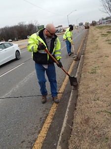 CATHY SPAULDING/Muskogee Phoenix Muskogee workers Stormie Rice, left, and Roy Smith scrape dirt off the curb of the Main Street median. Crews worked on the median's northbound side on Thursday afternoon.