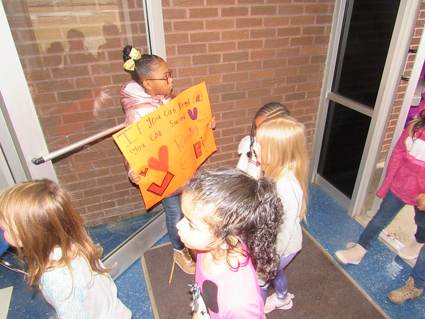 CATHY SPAULDING/Muskogee Phoenix<br /> Third-grader Kadence Brown holds a sign touting the value of reading while she holds the door open Friday for New Tech at Cherokee Elementary students participating in the March on Muskogee for Literacy.