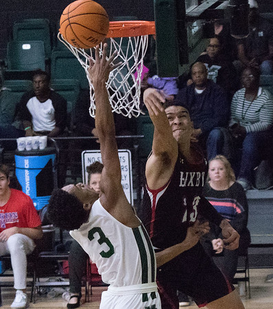 ABIGAIL WASHINGTON/Special to the Phoenix<br /> Muskogee's Xavier Brown goes up for a shot as Xavier Glenn of Bixby defends during Friday's game at Ron Milam Gymnasium.