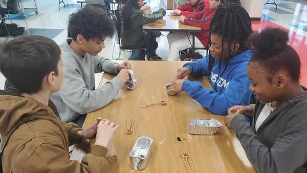 CHESLEY OXENDINE/Muskogee Phoenix<br /> (From left) Eighth-graders Austin Lyons, Kayden McGee, Everlon Ray and Shalena Clemson prepare aluminum steamboats using copper piping and candles at a Muskogee Dream It. Do It. program on Friday.