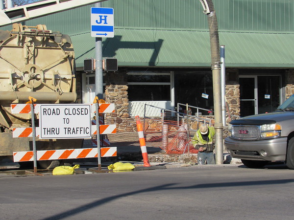 Staff photo by Cathy Spaulding<br /> Traffic on Okmulgee Avenue passes an NPL worker doing hydroexcavation at the corner of Okmulgee and 24th Street. He said the project might be finished within a month and a half.