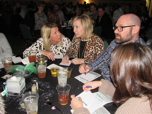 CATHY SPAULDING/Muskogee Phoenix<br /> Tony Goetz Elementary School teachers Jennifer Hunter, left and April Roberts discuss the answer to a Trivia Night question while Justin Roberts ponders the answer. They competed against 39 other teams during the Trivia Night challenge.The annual event benefits the Education Foundation of Muskogee.
