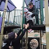 """KENTON BROOKS/Muskogee Phoenix<br /> Keely Vance, left, reaches up ready to catch Hazel Ballard while Caleb Ballard helps Hazel get a grip on the pole to slide down on playground equipment at Spaulding Park on Wednesday. The Ballards and Vances forgot about their Christmas gifts for the time being to enjoy a cool, crisp day at the park and """"to run off some energy,"""" Brittany Ballard said. The children played on the swings, slid down poles and then played in piles of leaves during their day in the park."""