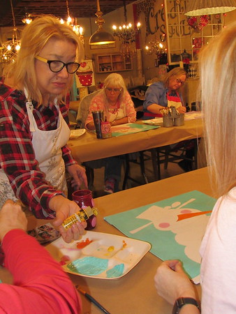 """Hope Farmer squeezes paint for one of her participants in a Creative Soul painting session. Farmer said she sees herself as a """"servant"""" helping people get creative."""