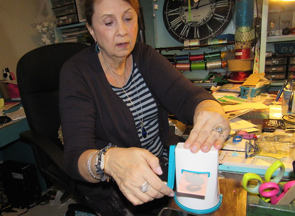 Photo by Cathy Spaulding<br /> Nancy McLemore cranks out a cut flamingo pattern on a die cutter. She uses the cutter for cards she makes friends.
